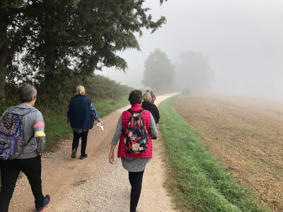 women walking along road into fog umbria italy walking vacation